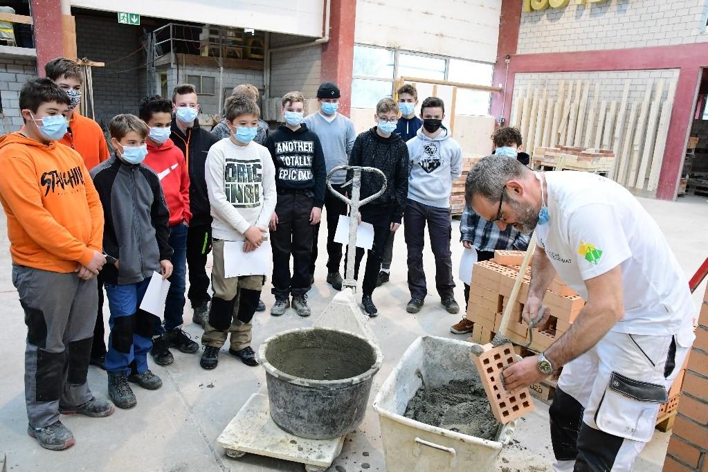 Bild: Chefinstruktor Thomas Arpasi demonstriert den Jugendlichen das professionelle Aufziehen einer Stossfuge mit der Maurerkelle